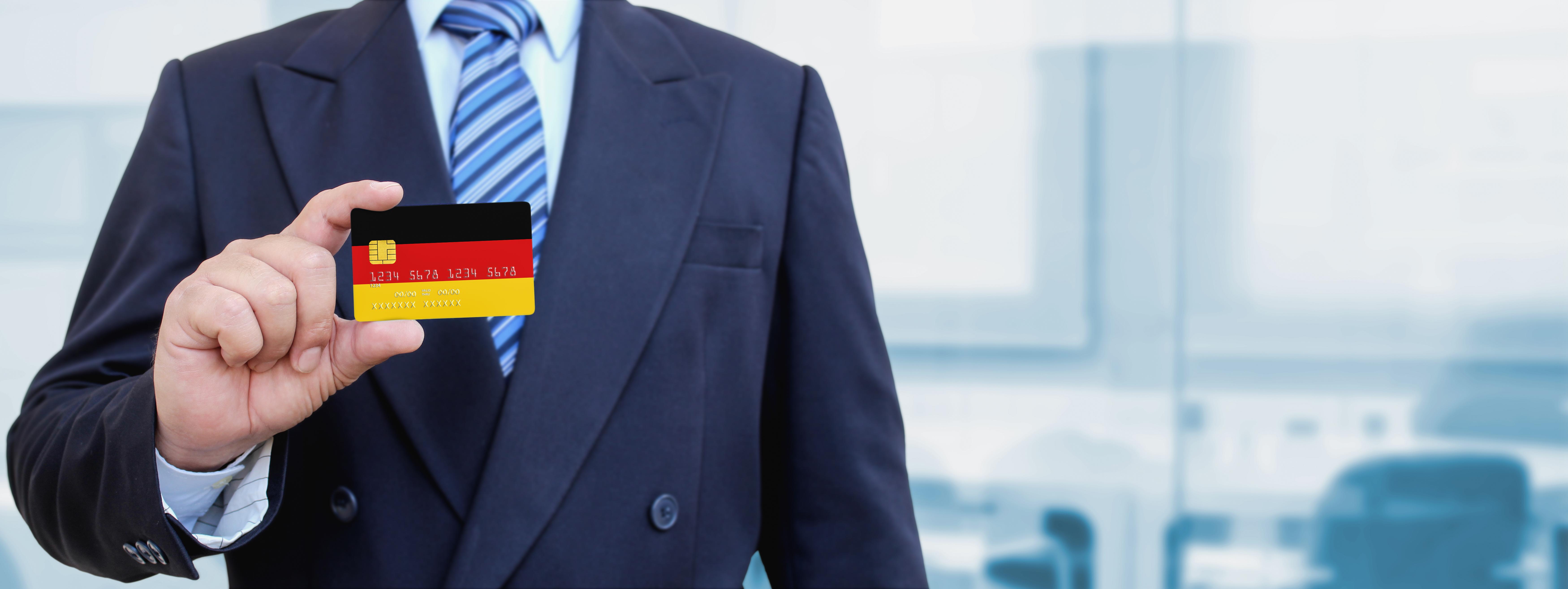 Бизнесмен с флагом Германии, куда можно переехать по бизнесу
