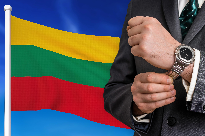 Бизнесмен на фоне флага Литвы, где иностранцы могут открыть бизнес