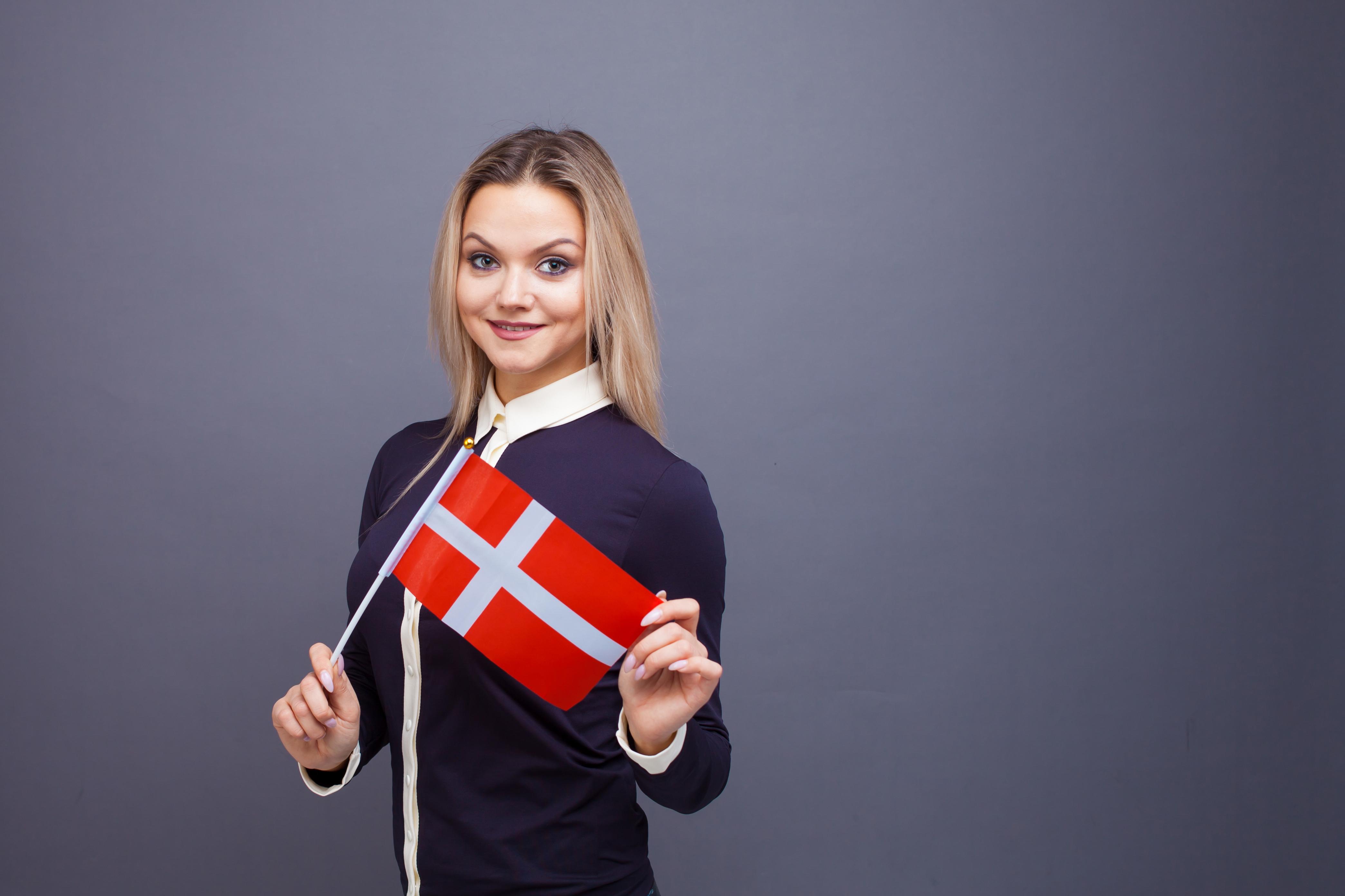 Девушка с флагом Дании, переехать в которую можно по трудоустройству
