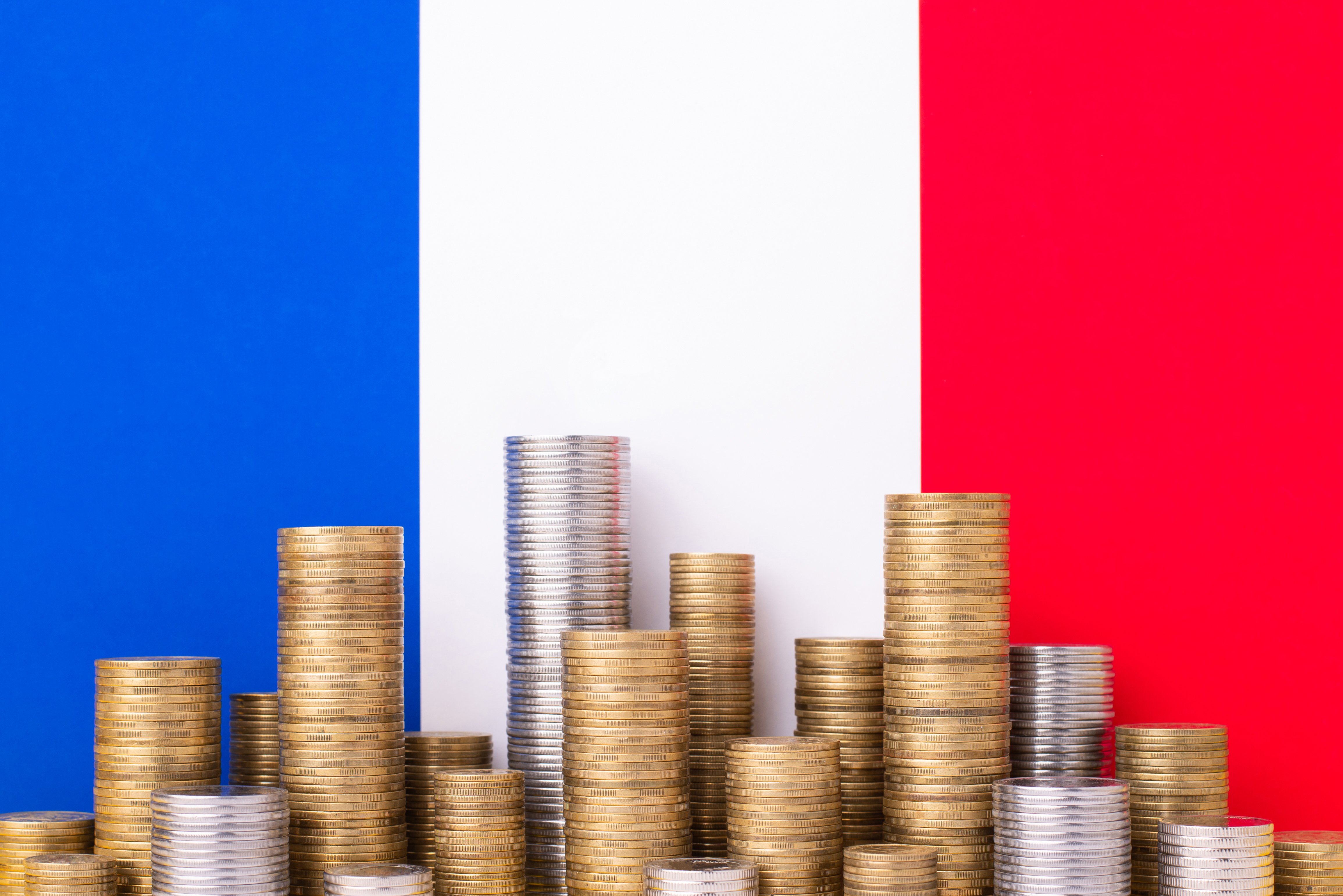 Монеты и флаг Франции, ВНЖ которой можно получить через инвестиции