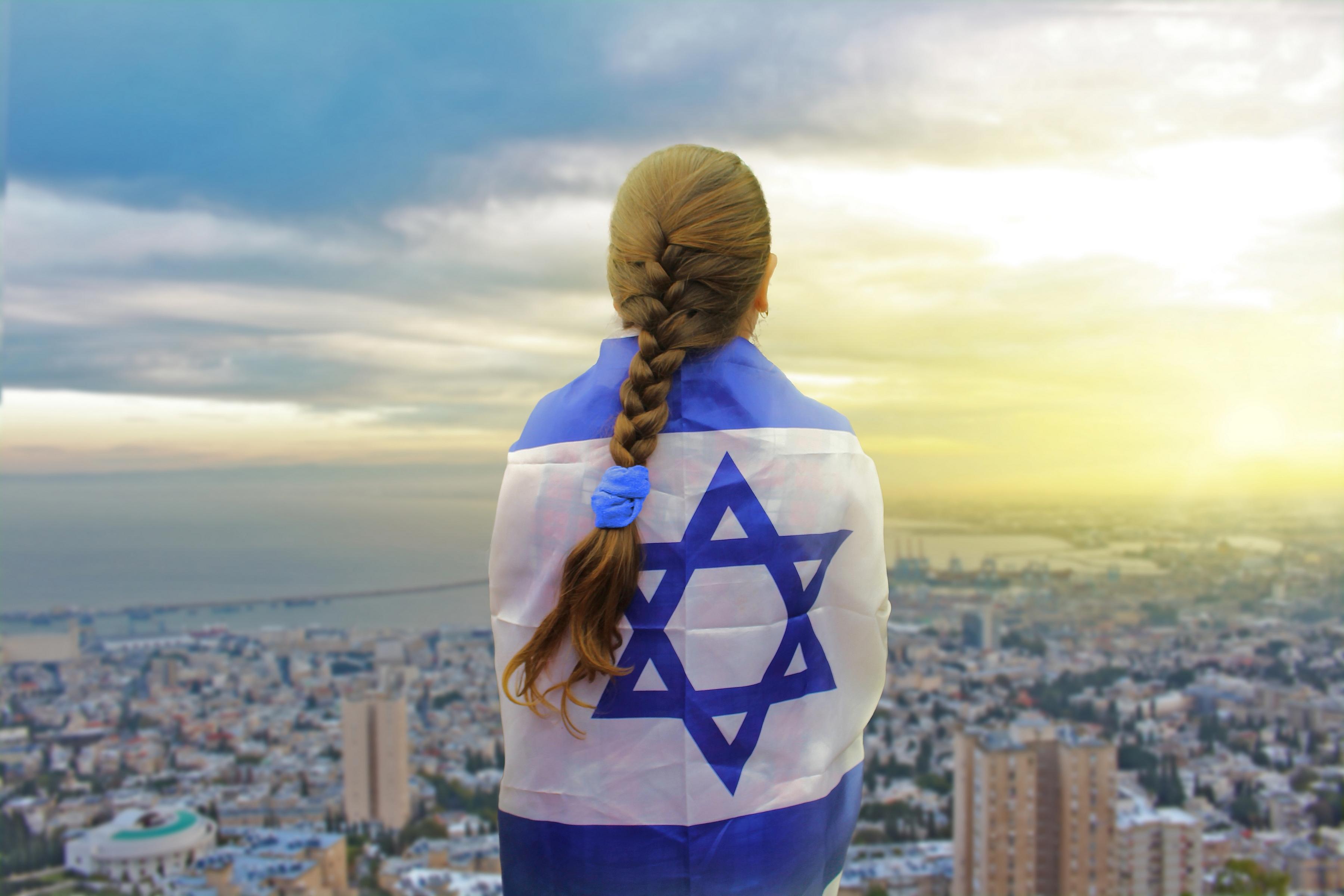 Девушка, завернутая в флаг Израиля, куда на ПМЖ можно переехать из России