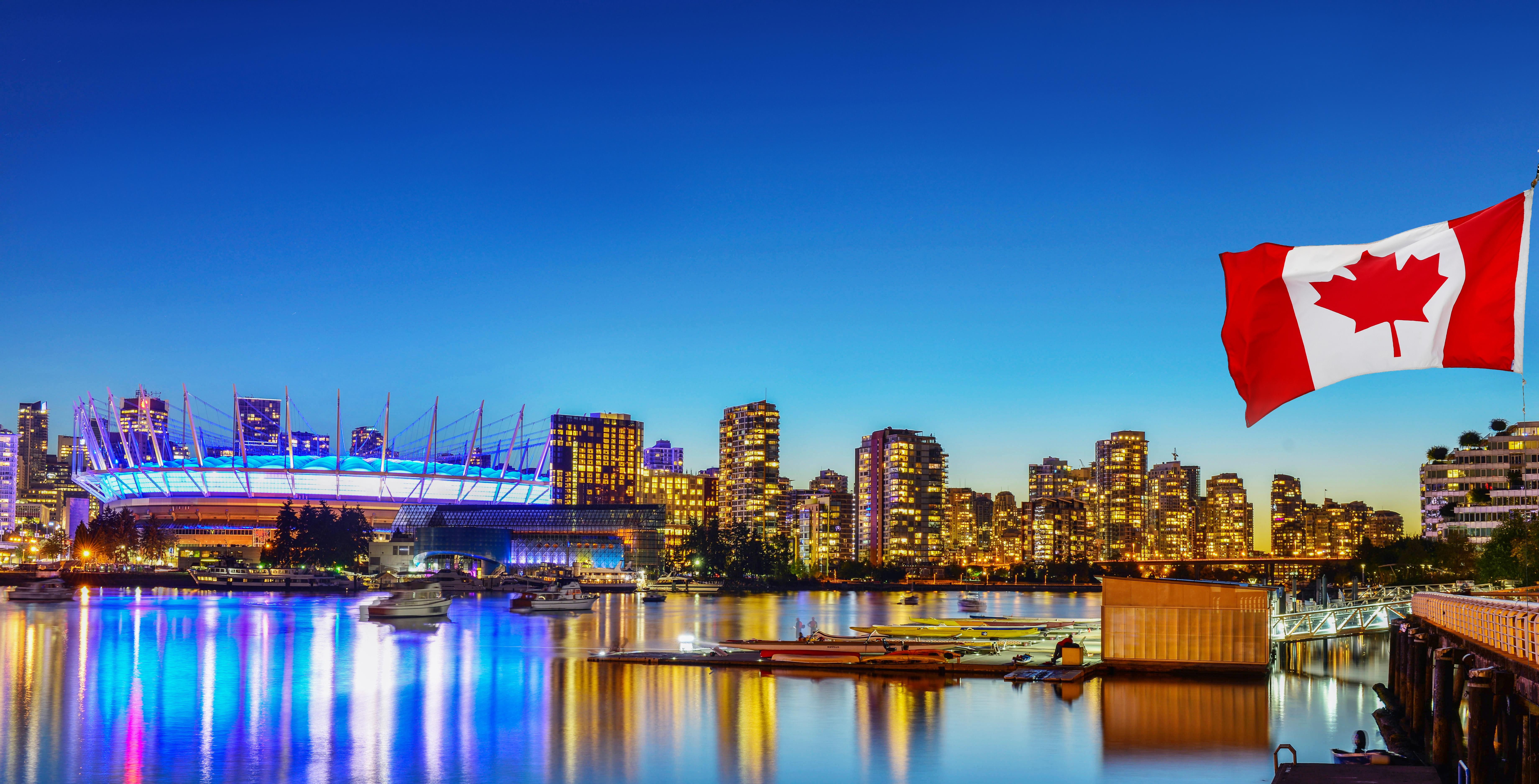 Канадский флаг на фоне Ванкувера в Канаде, куда на ПМЖ можно переехать из России