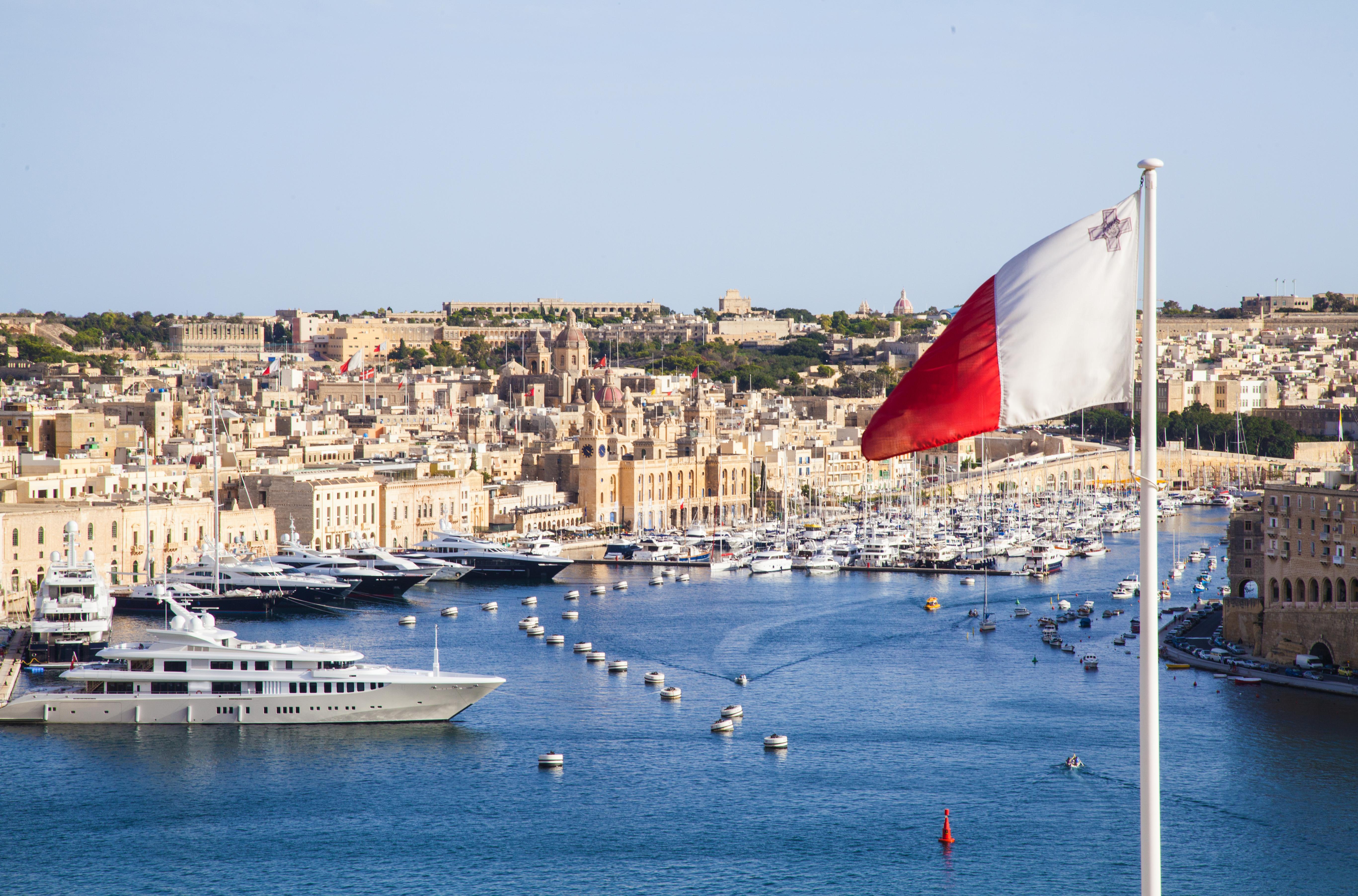 Флаг на фоне Валлетты, столицы Мальты, ВНЖ которой могут получить иностранцы
