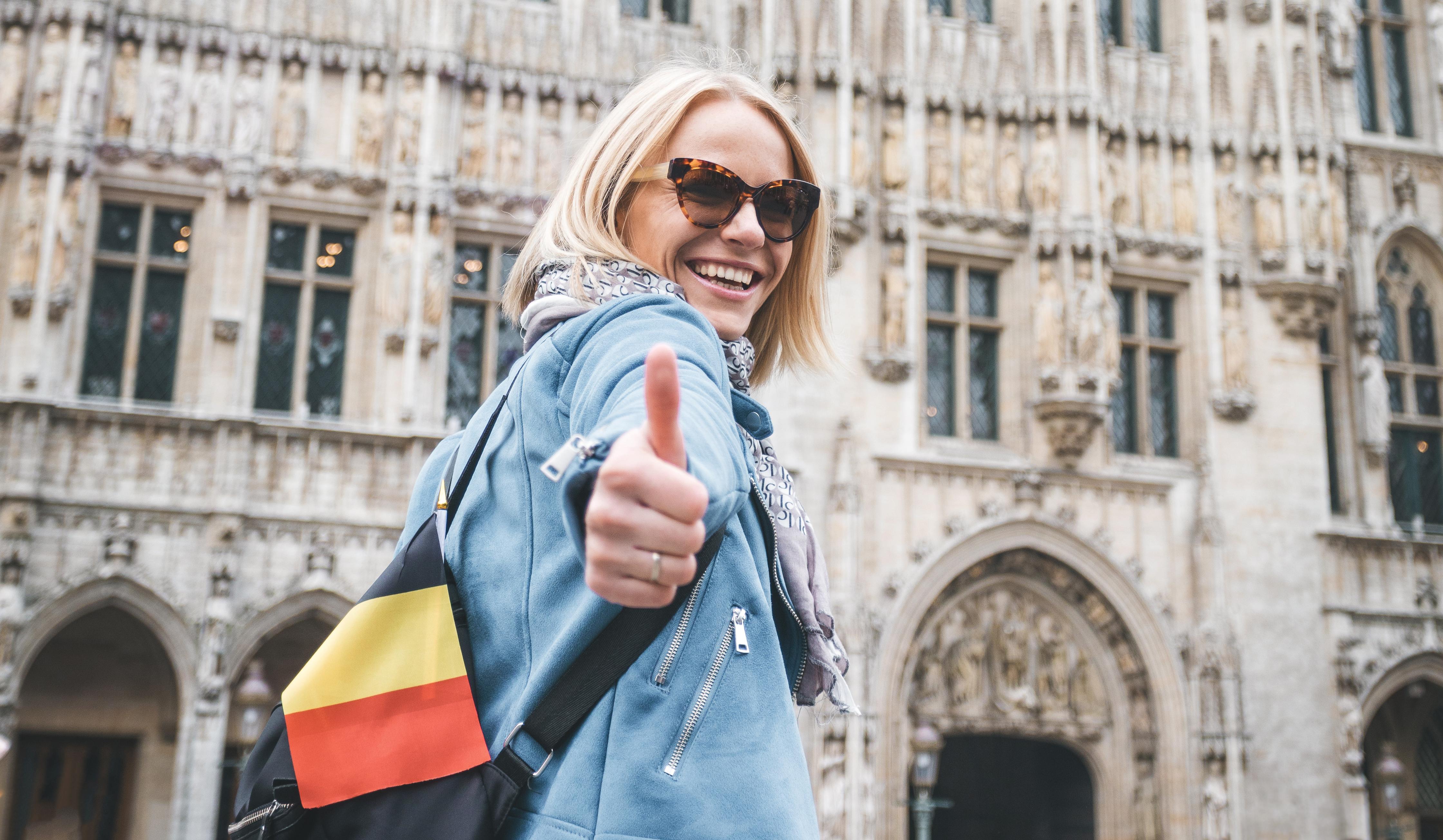 Девушка с флагом Бельгии, ВНЖ которой могут оформить иностранцы