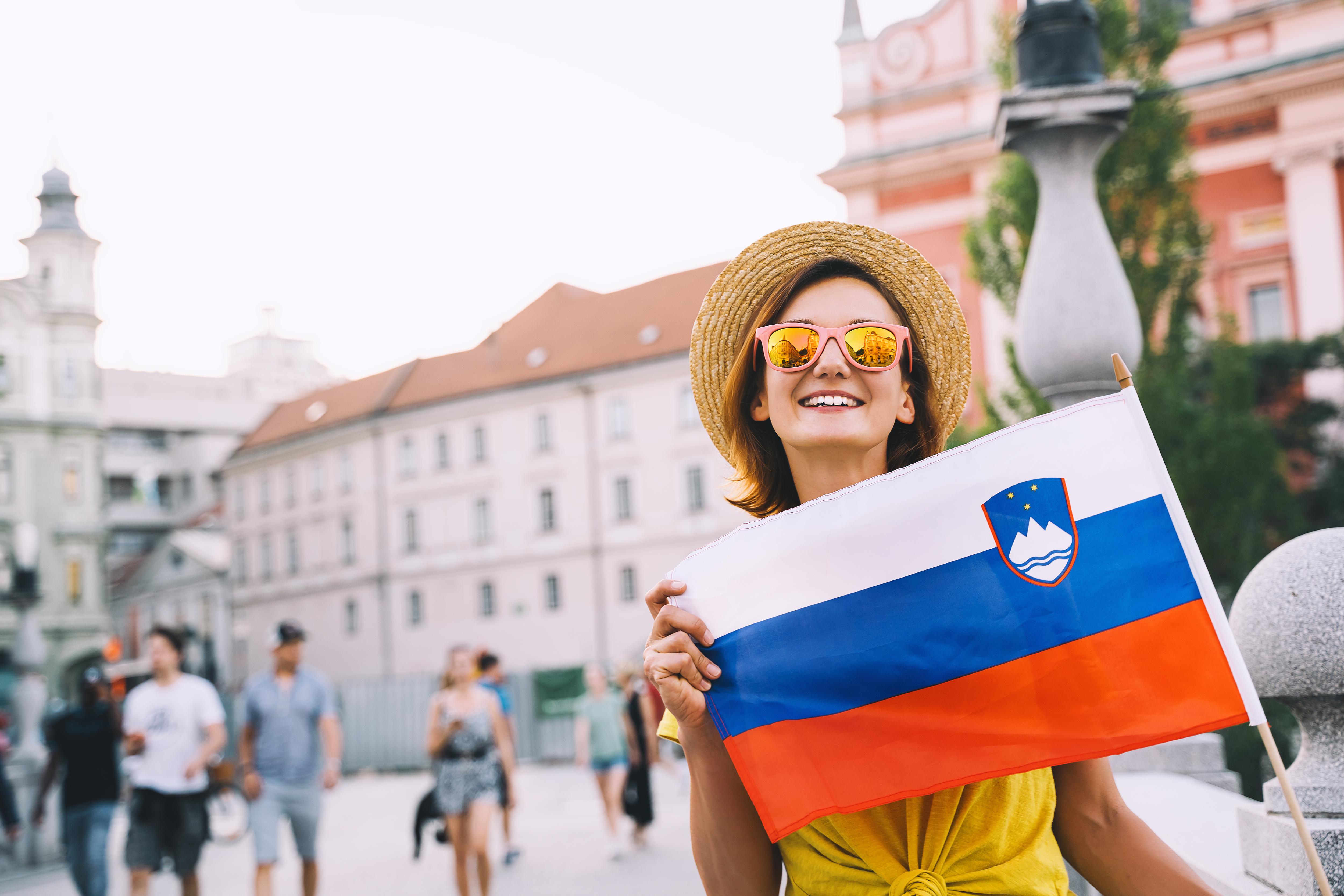 Девушка с флагом Словении, где можно оформить ВНЖ для иностранцев