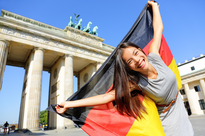 Девушка с флагом Германии, переехать в которую могут иностранцы
