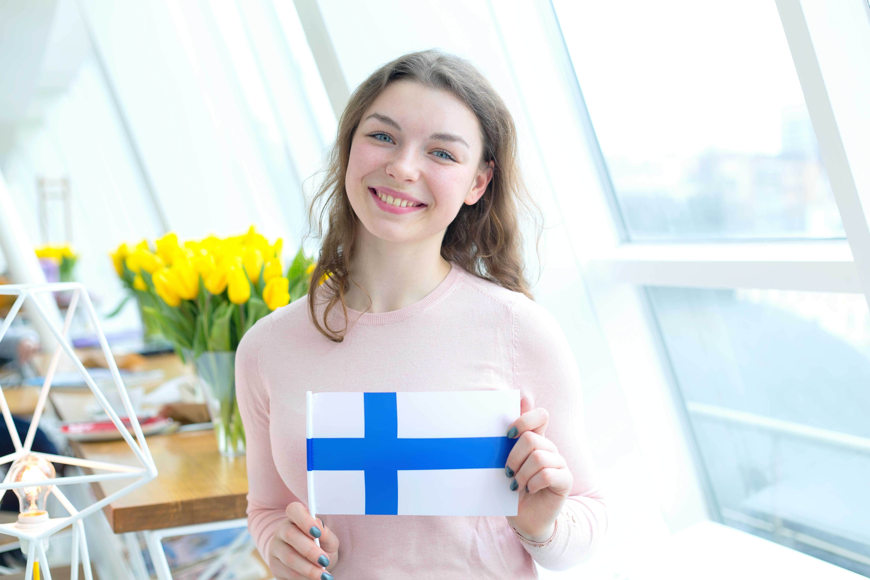 Студентка держит флаг Финляндии, куда могут уехать на учебу иностранцы