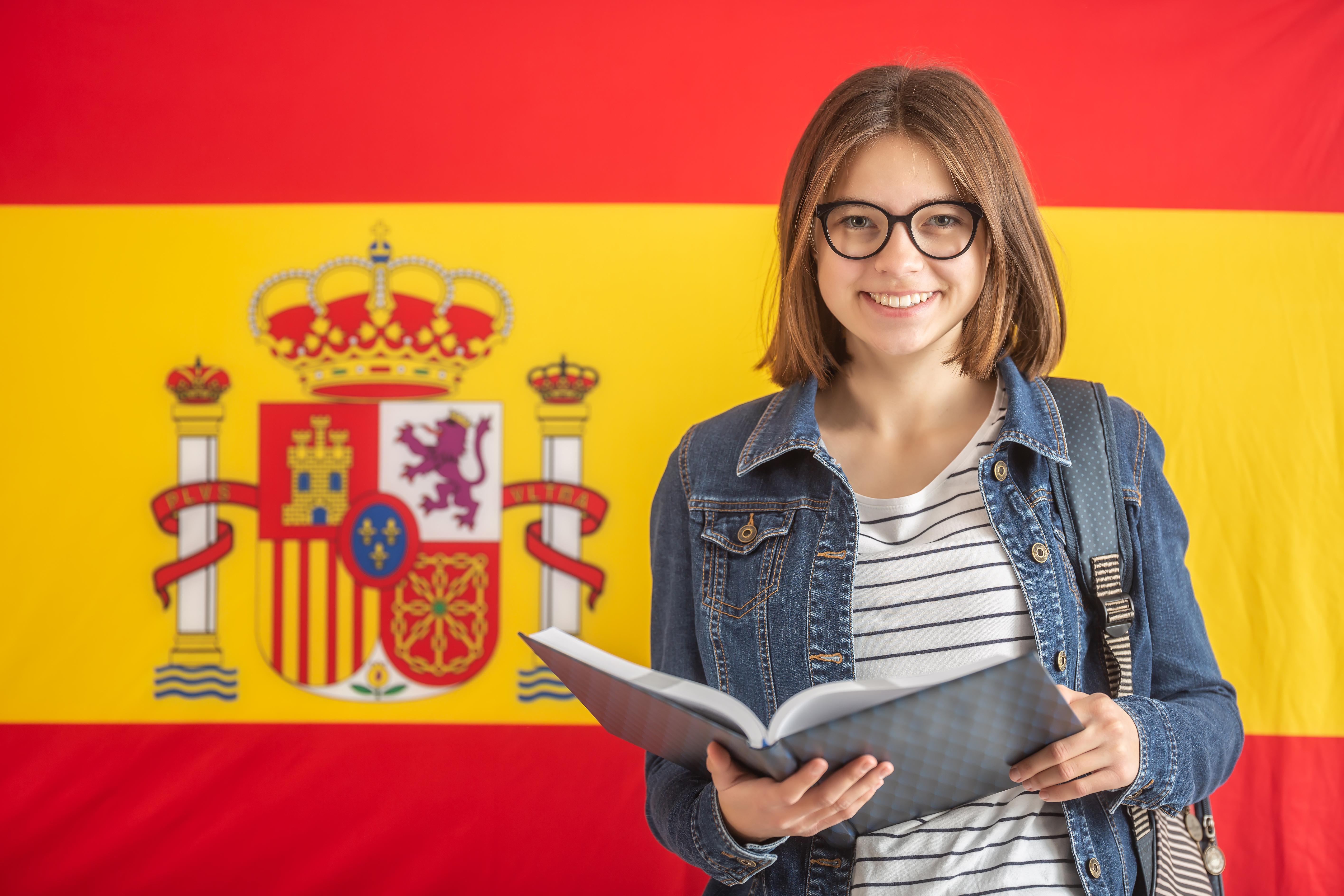 Девушка на фоне флага Испании, где могут обучаться иностранцы