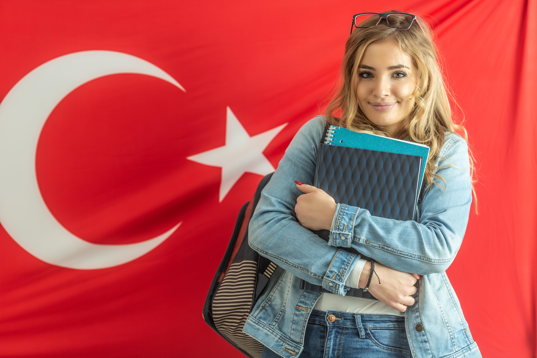 Студентка на фоне флага Турции, куда могут уехать на учебу иностранцы