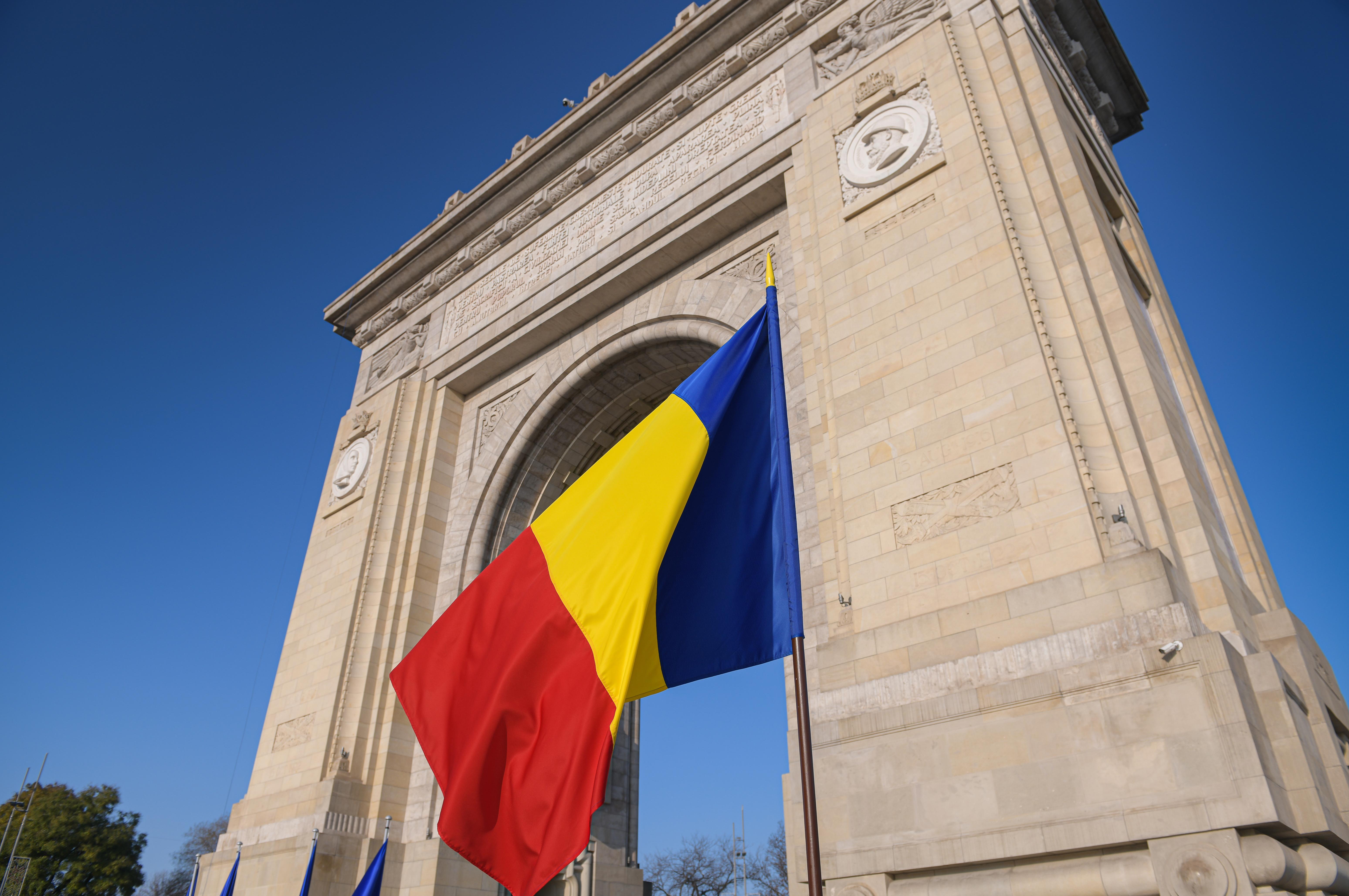 Флаг на фоне Триумфальной арки в Румынии, стране, в которой можно оформить ВНЖ