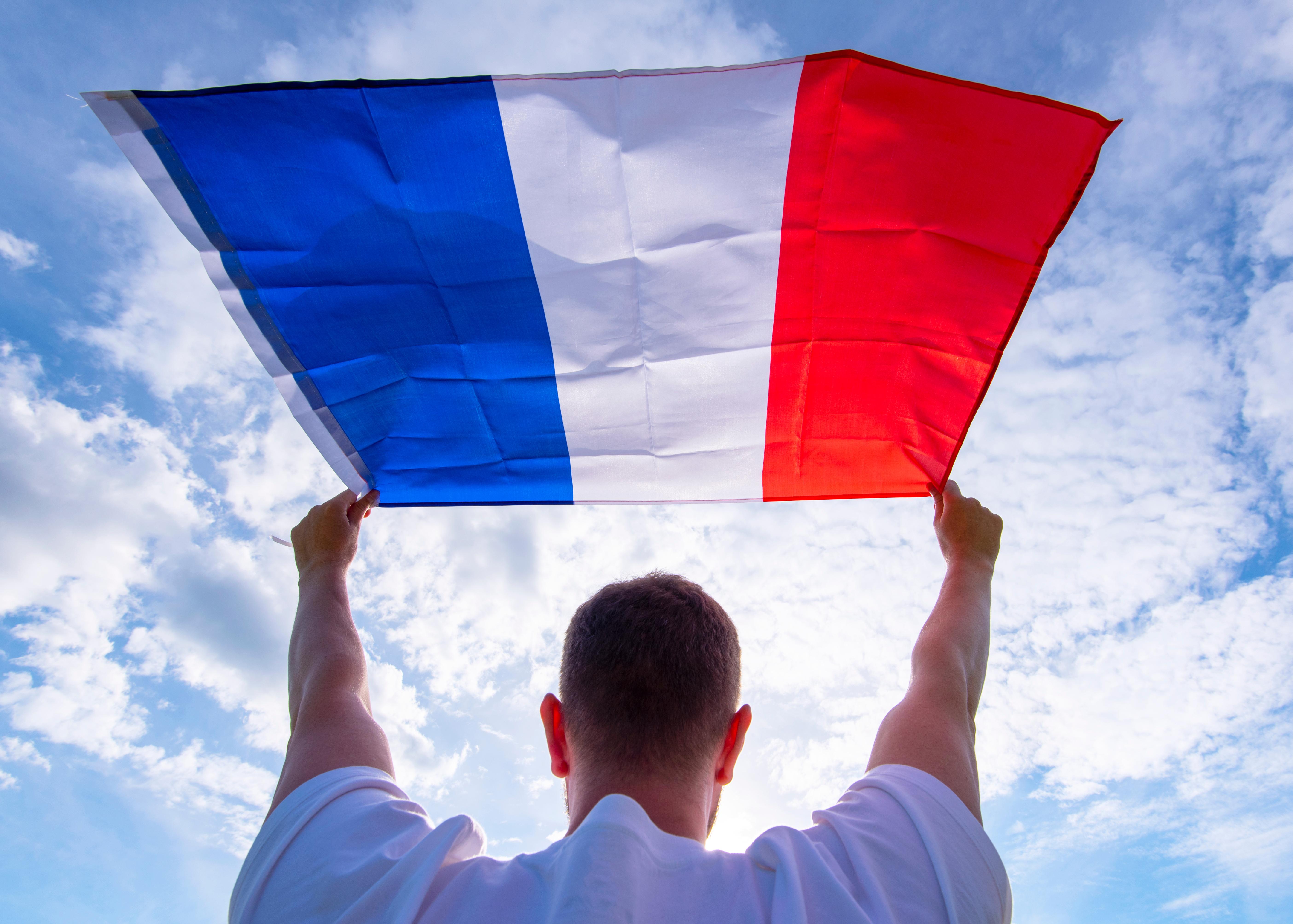 Парень с флагом Франции, паспорт которой можно получить согласно отзывам