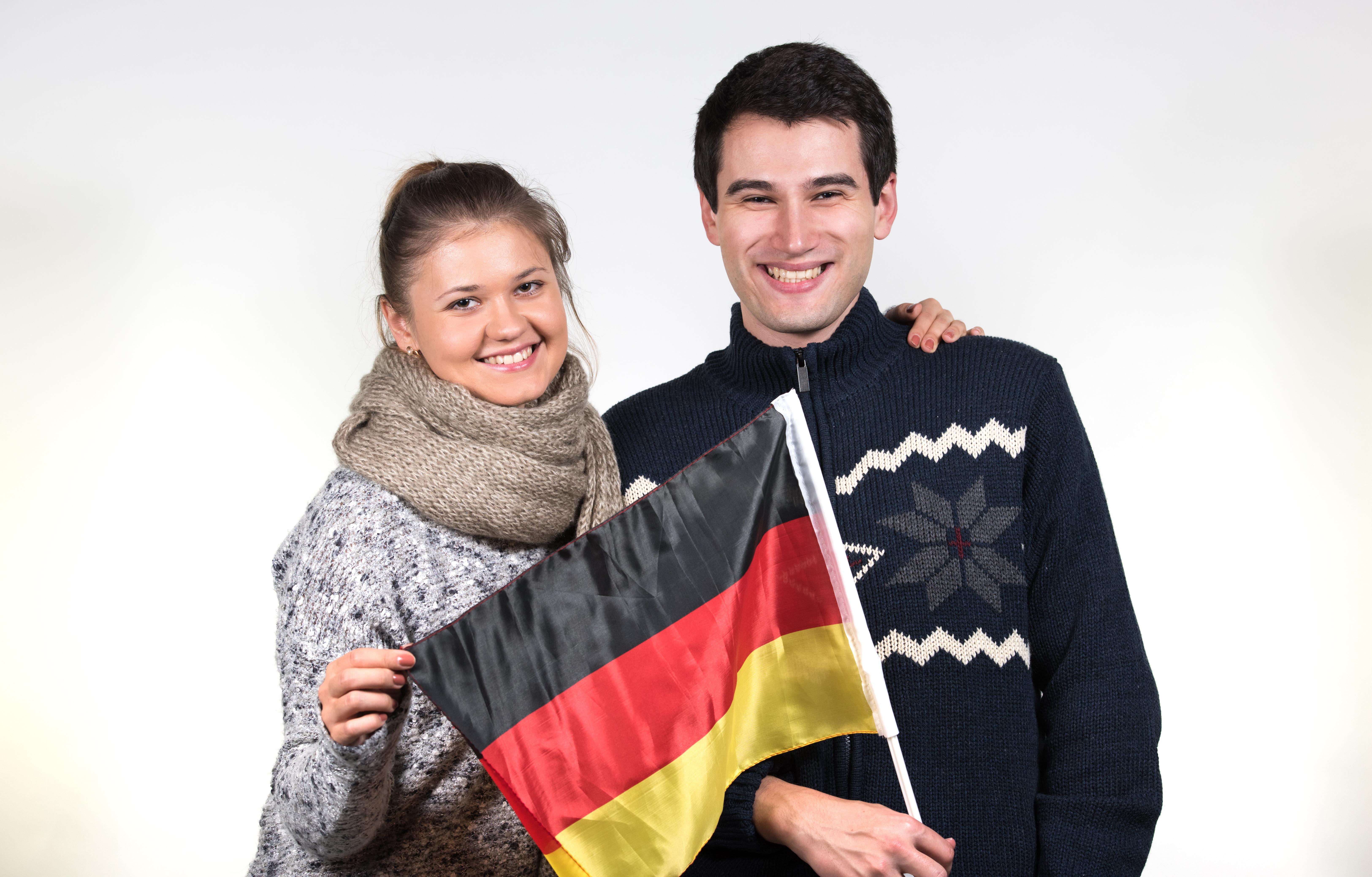 Молодая пара с флагом Германии, паспорт которой можно получить согласно отзывам
