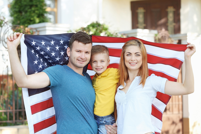 Семья с флагом США, куда могут иммигрировать иностранцы