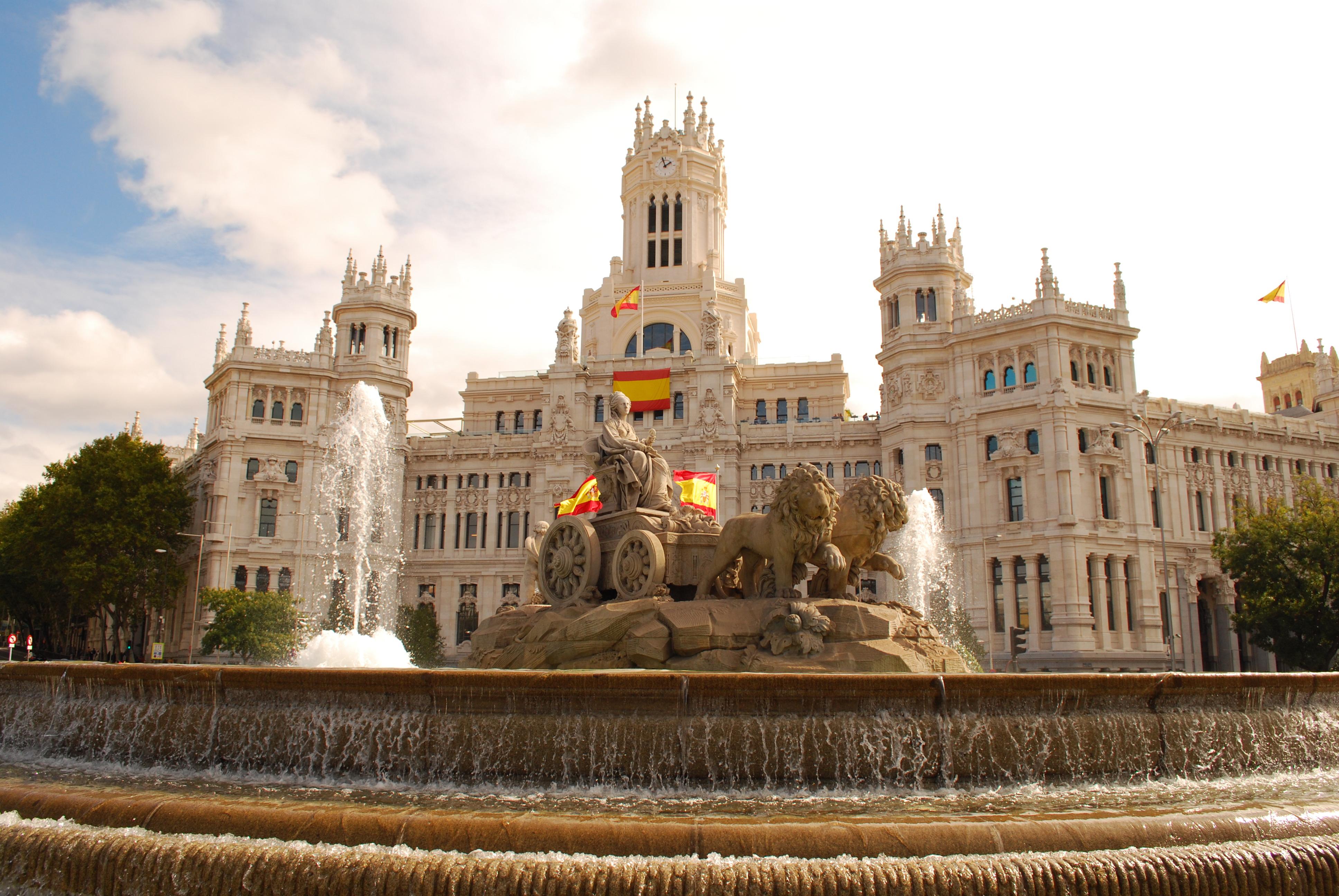 Испанские флаги возле фонтана Сибелес в Испании, ПМЖ которой могут получить иностранцы