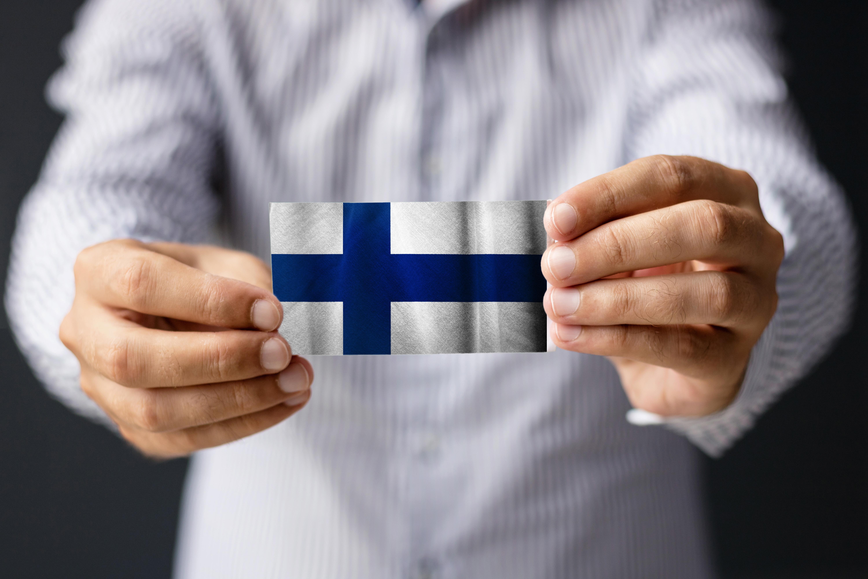 Мужчина держит флаг Финляндии, страны, где работа доступна для иностранцев