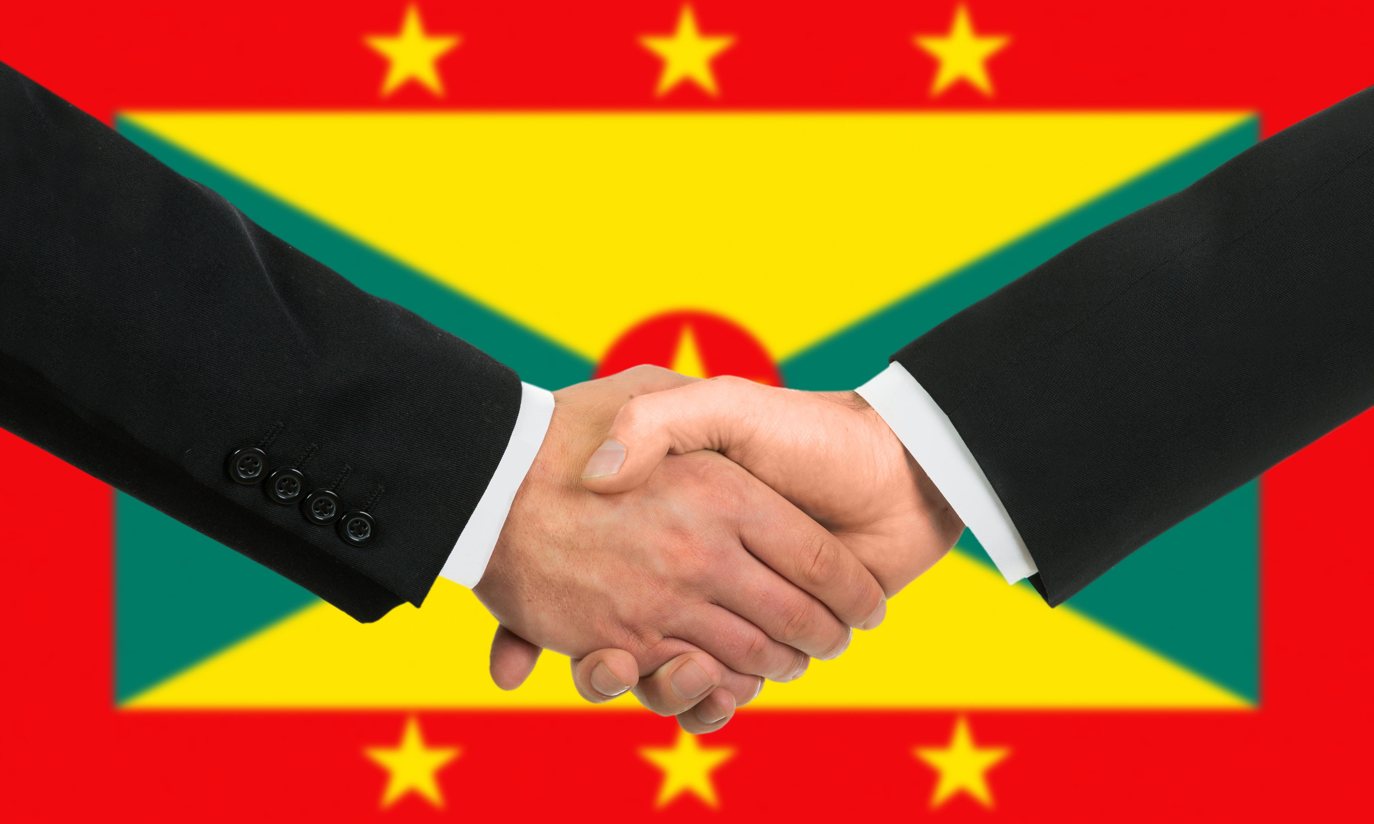 Рукопожатие на фоне флага Гренады, куда можно переехать по трудоустройству