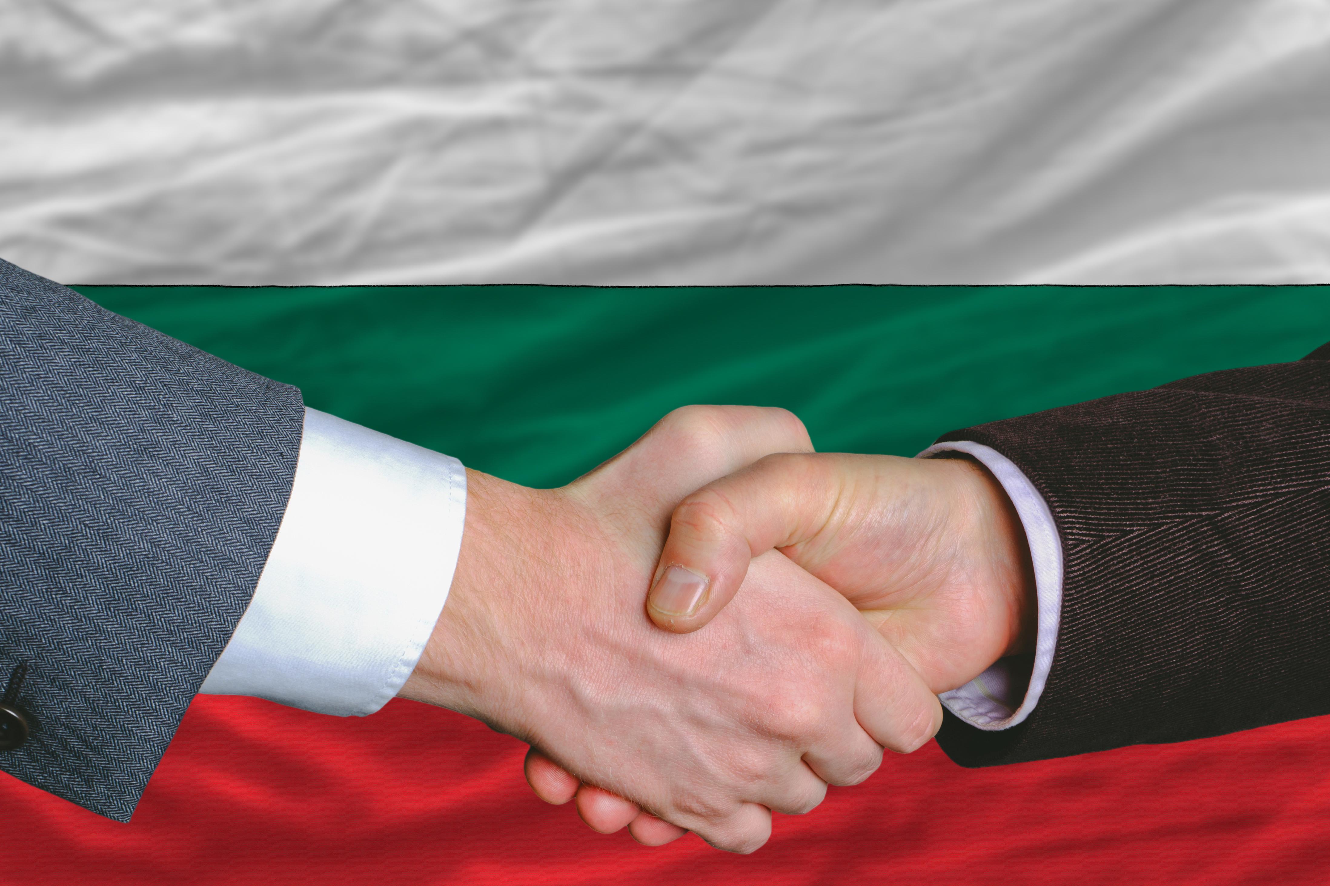 Рукопожатие на фоне флага Болгарии, где работа доступна для иностранцев