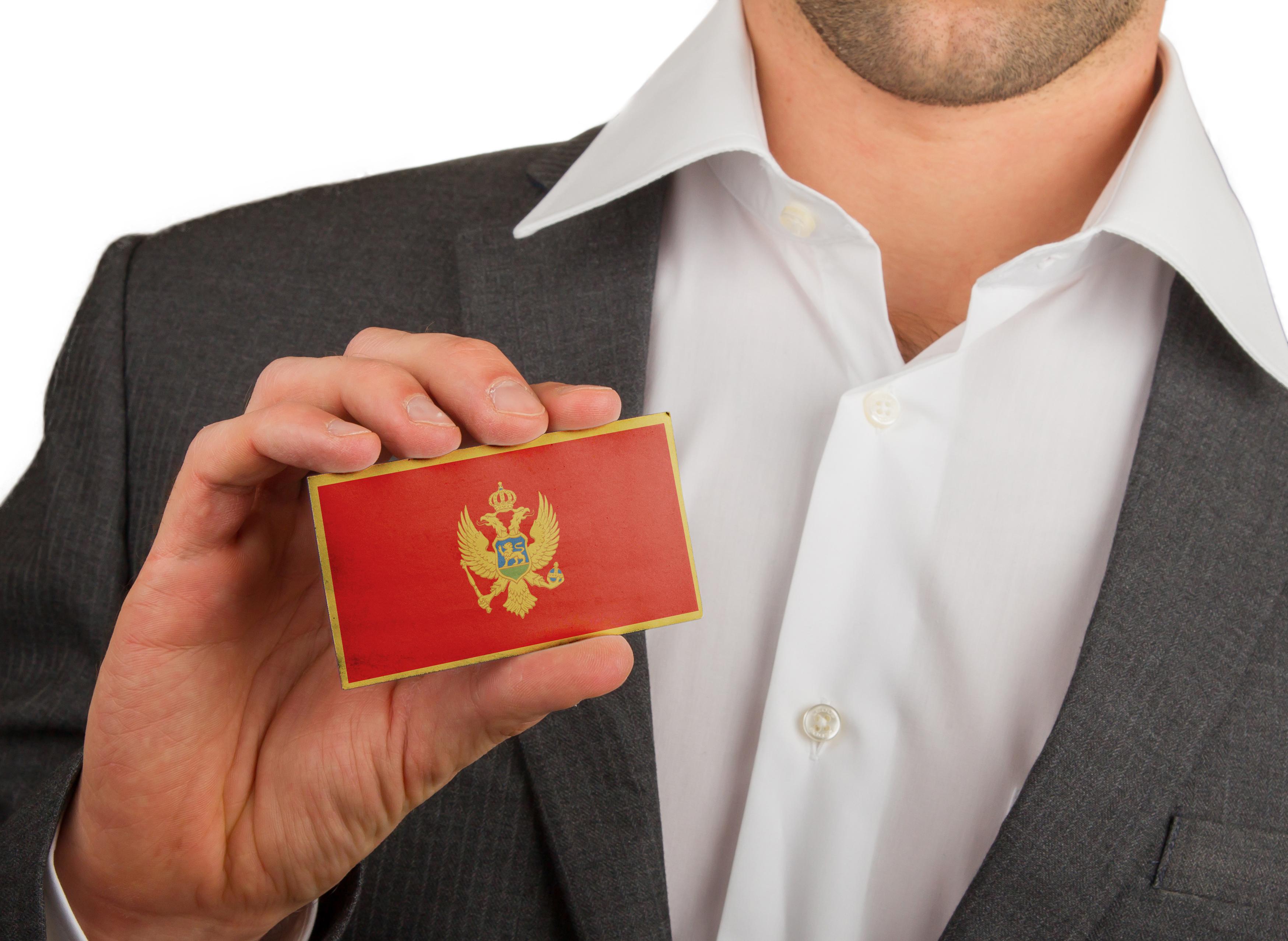 Мужчина с флагом Черногории, где работа доступна для иностранцев