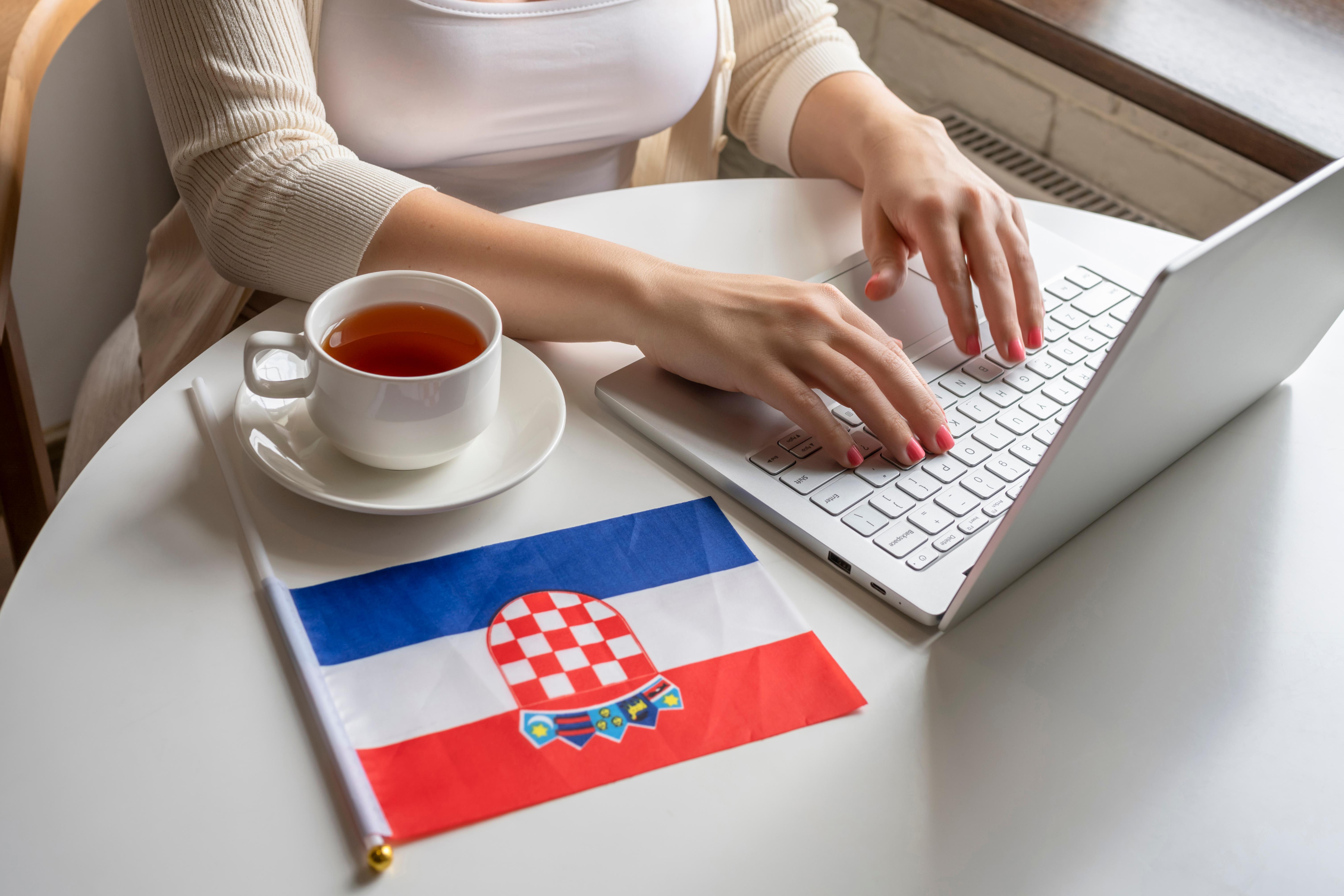 Девушка за ноутбуком возле флага Хорватии, где работа доступна для иностранцев