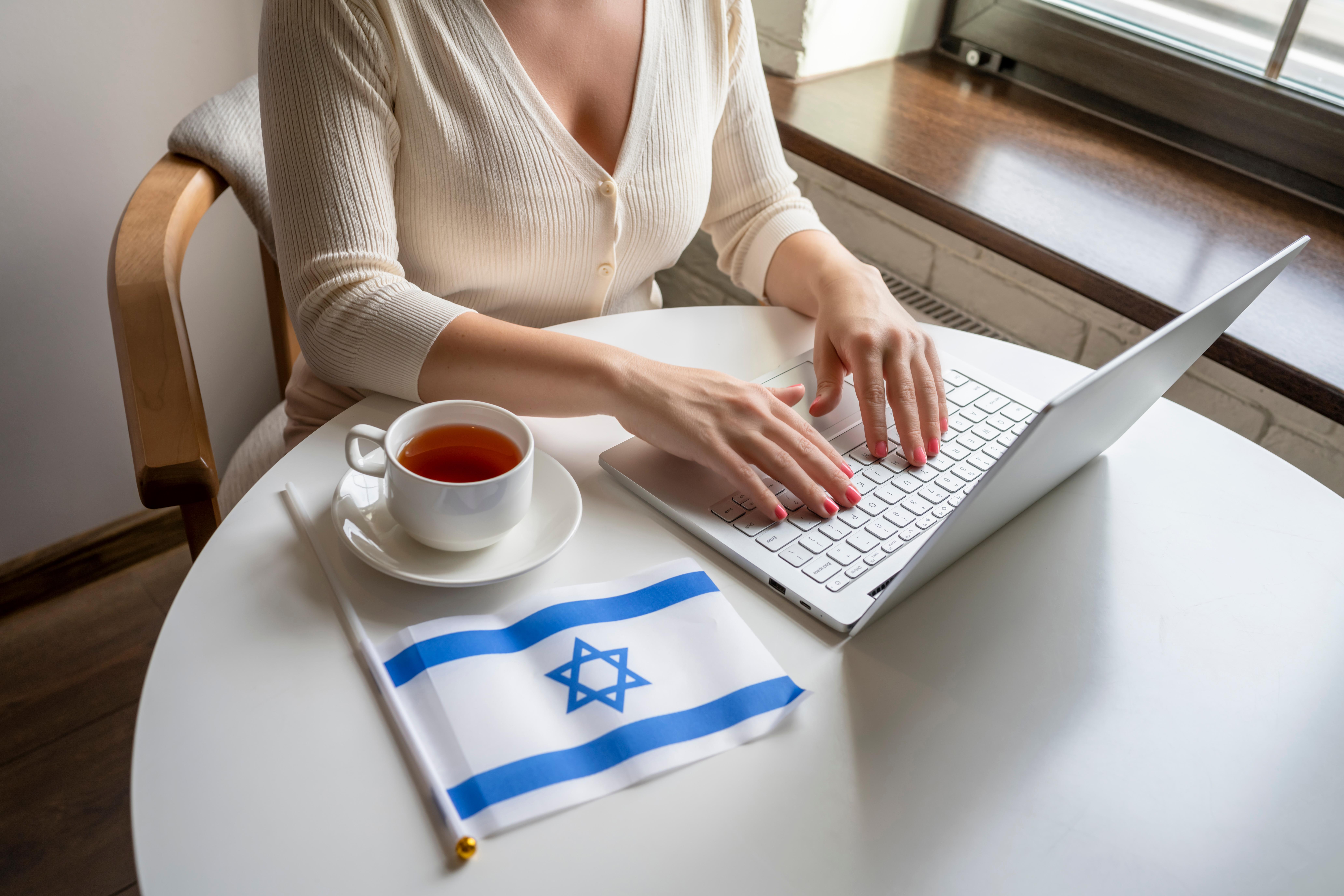 Девушка за ноутбуком возле флага Израиля, где работа доступна для иностранцев
