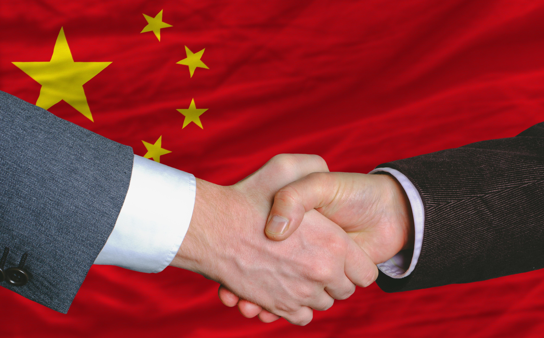 Рукопожатие на фоне флага Китая, куда можно переехать по трудоустройству