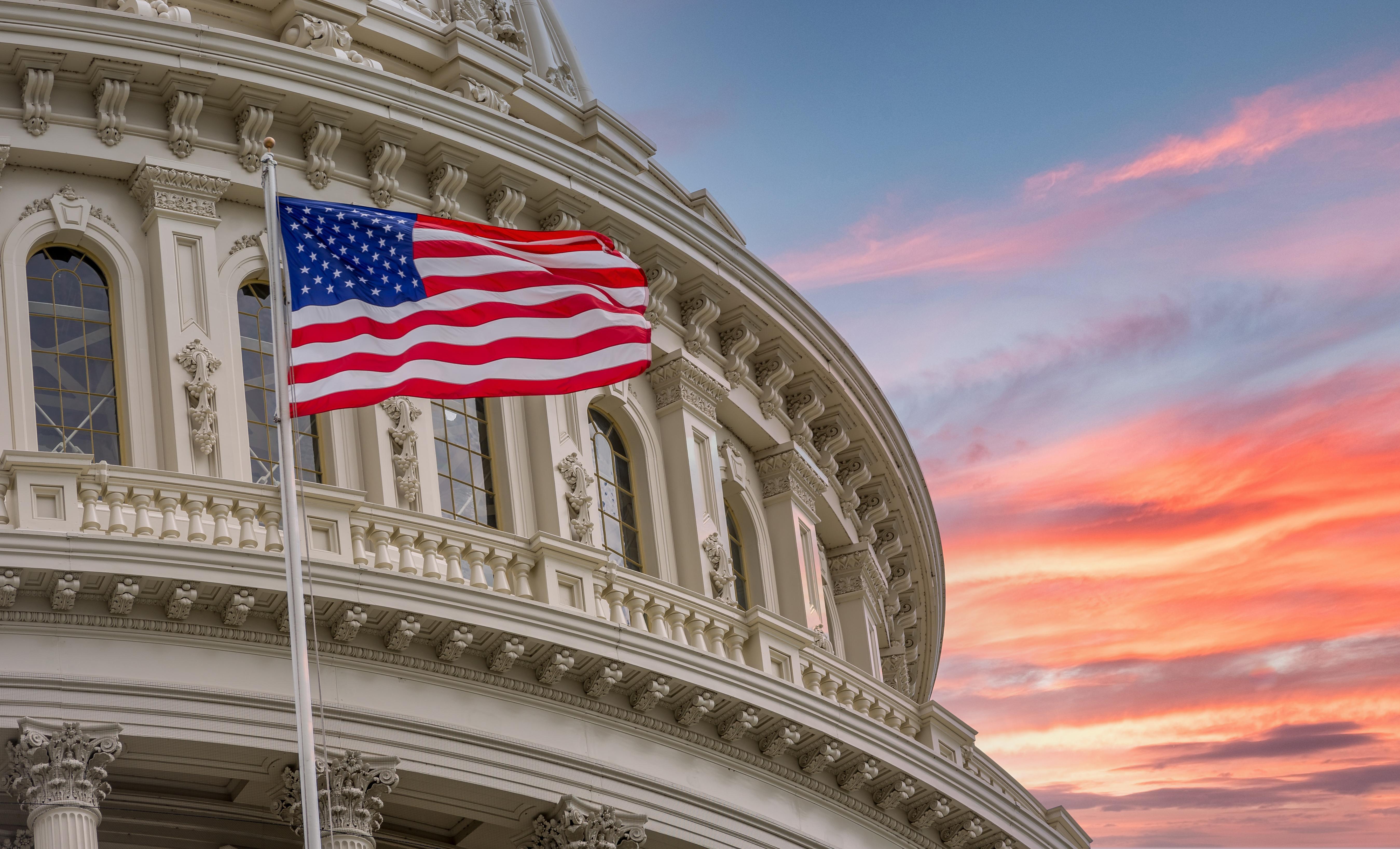 Американский флаг возле госздания, которое выдает грин-карту иммигрантам