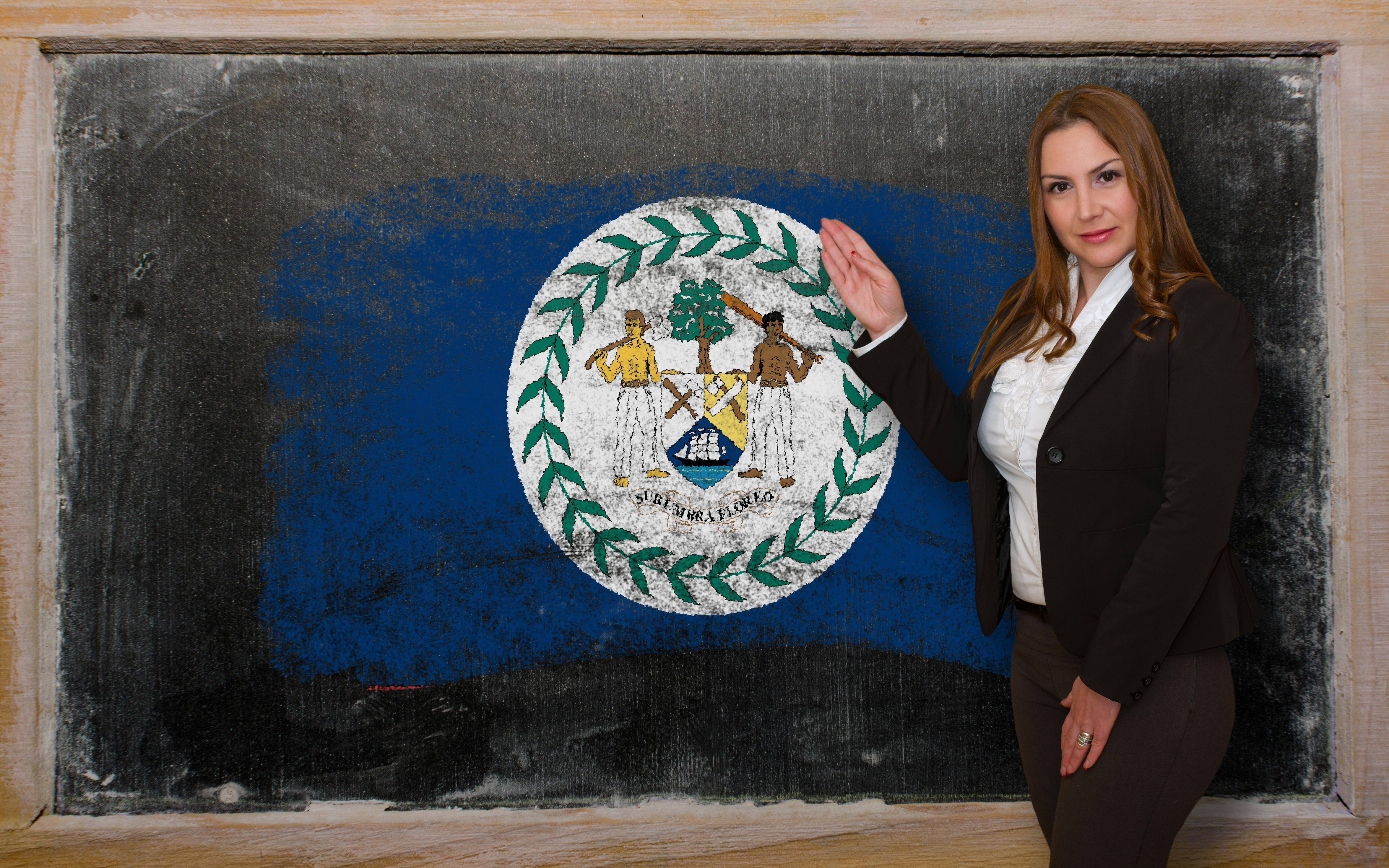 Женщина возле флага Белиза, где есть возможность обучаться для иностранцев