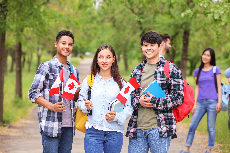 Студенты с канадскими флагами, которые могут переехать в Канаду по учебе