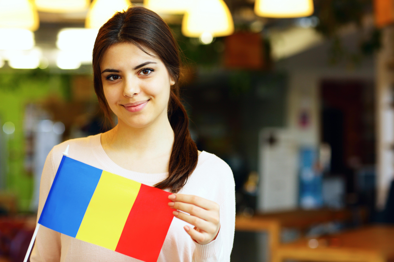 Студентка держит флаг Румынии, куда могут уехать на учебу иностранцы