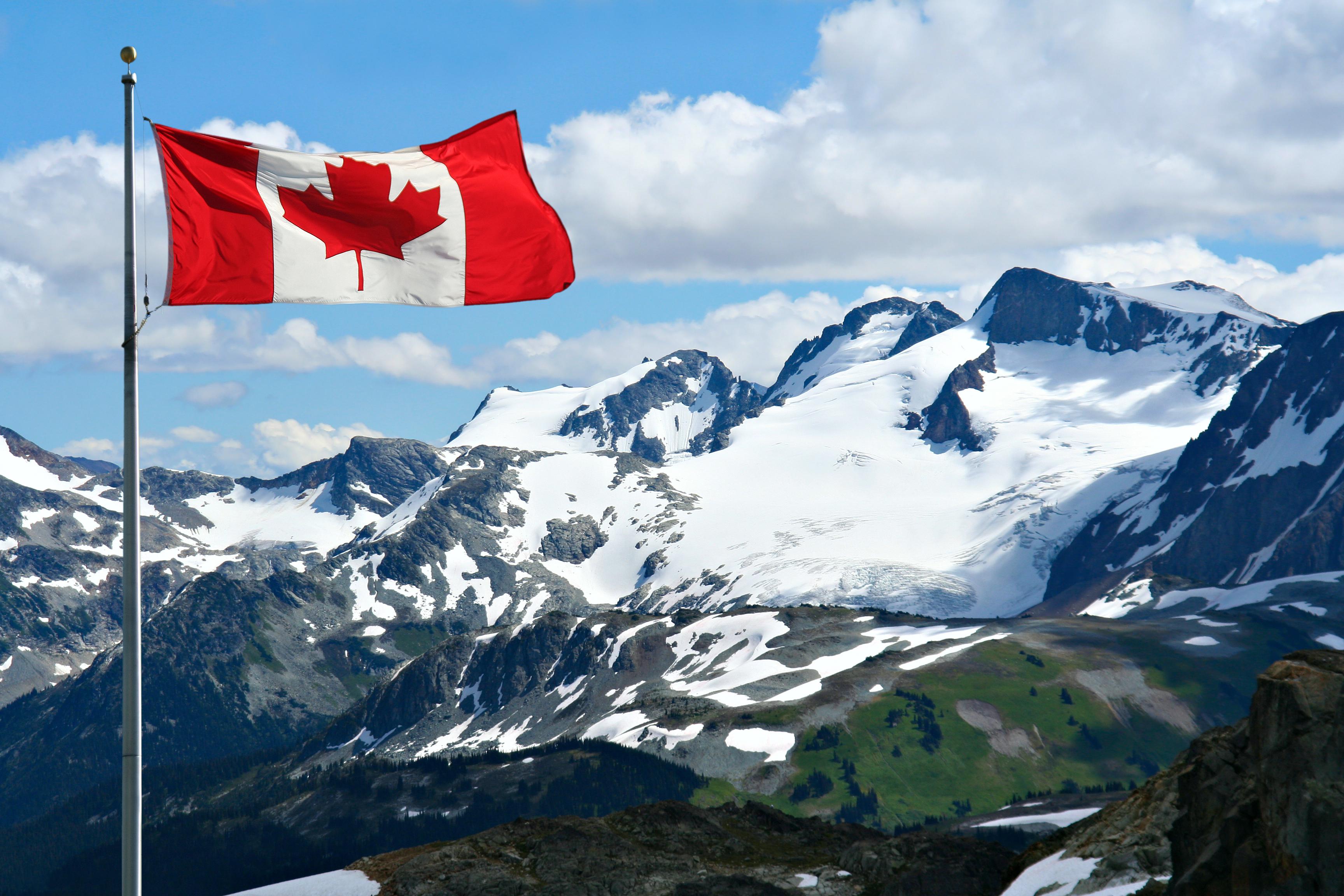 Флаг на фоне гор в Канаде, где россияне могут получить ВНЖ