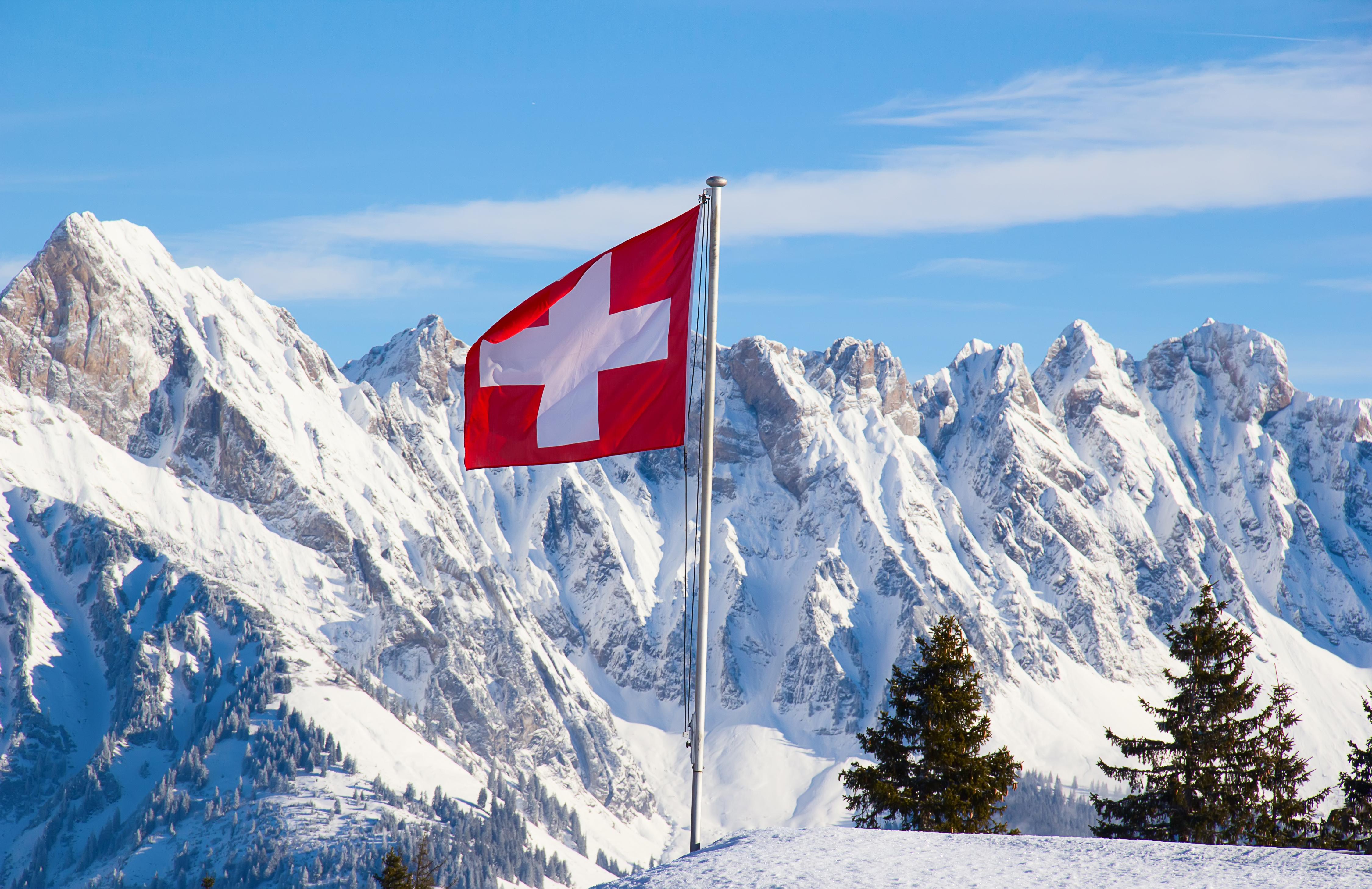 Флаг на фоне гор в Швейцарии, ВНЖ которой могут получить россияне, украинцы и белорусы