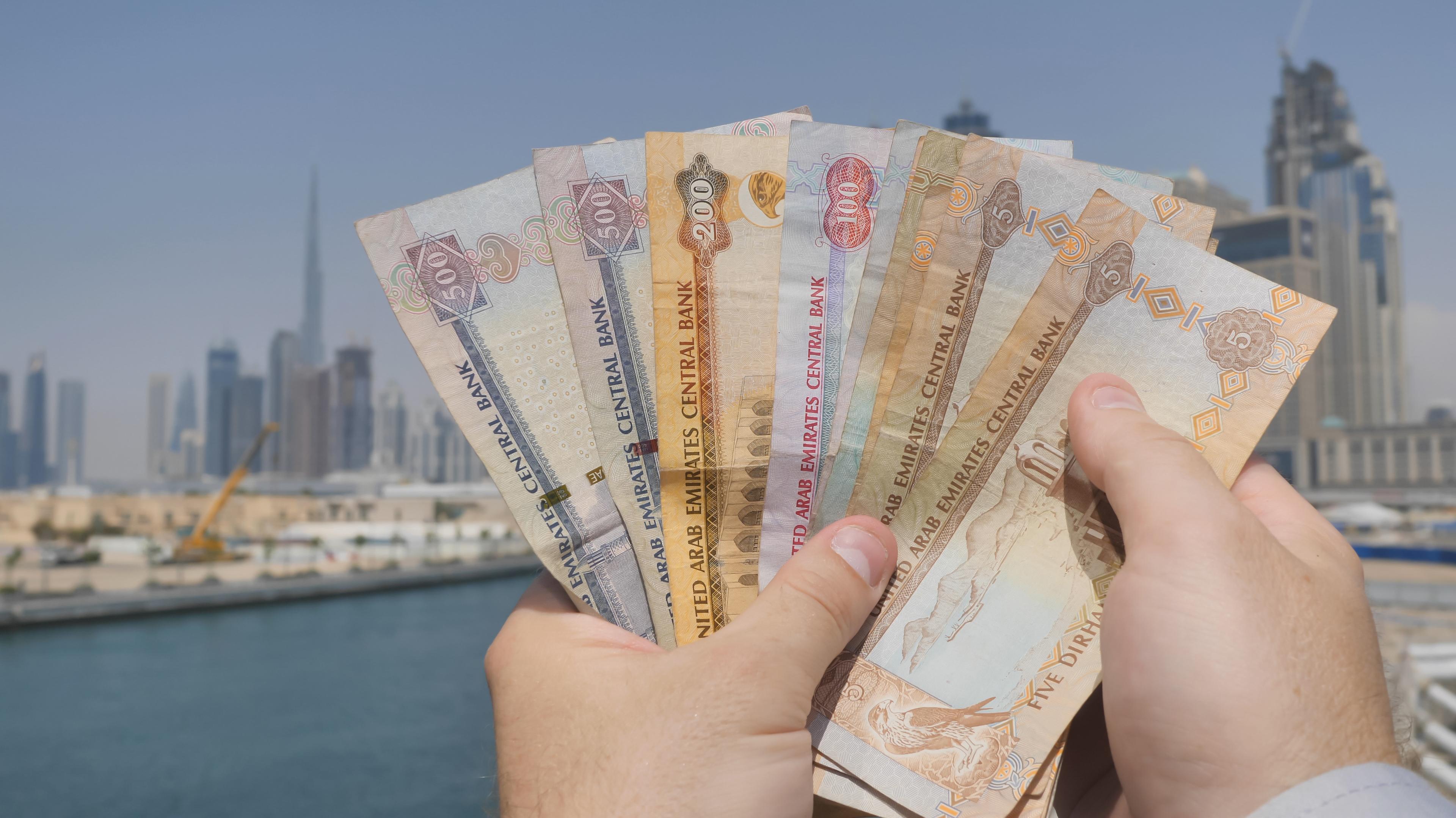 Мужчина держит в руках зарплату, которую он получил в Дубае