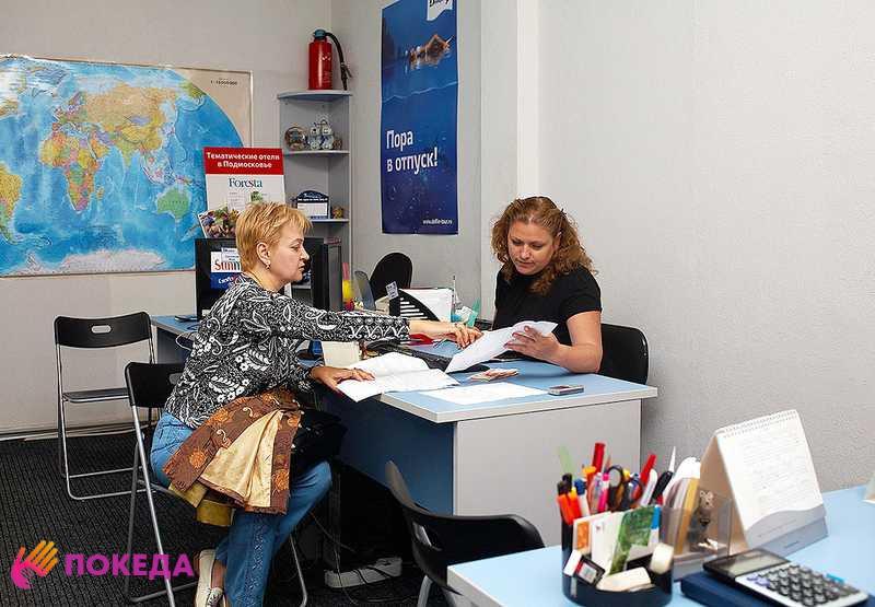 Женщина с в турагентстве разговаривает с агентом